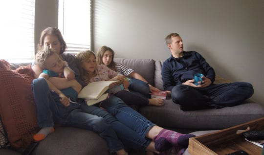 Brighton Township residents Sarah and Nick Barish, with their children, from left, Pierce, 5, Ada, 8, and Madelyn, 9, watch a YouTube recording of the 2|42 Church service aired at 10:30 a.m. Sunday, May 10, 2020.