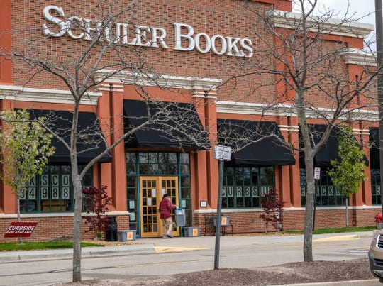 A Schuler Books employee retrieves an empty, numbered bin after a customer picked up an order for curbside pickup Sunday, May 10, 2020.