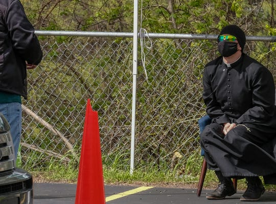 Rev. Mark Rutherford of St. Mary Church in Williamston, listens to a man at a drive-through confession event set up in a parking lot on Saturday, May 9, 2020.