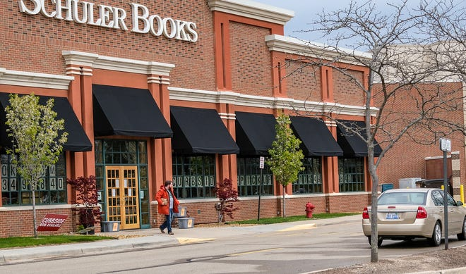A man picks up his curbside book order at Schuler Books at the Meridian Mall Sunday, May 10, 2020.
