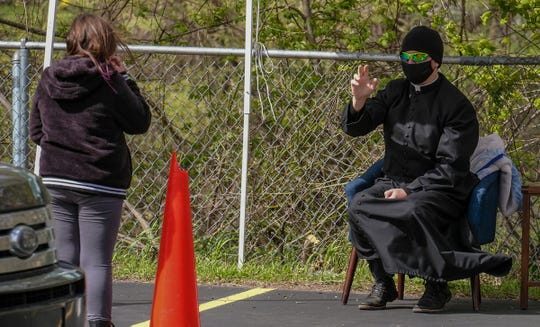 Rev. Mark Rutherford hears confession in the parking lot of St. Mary Catholic Church Saturday, May 9, 2020.