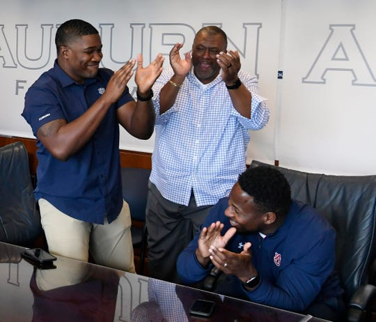 Auburn coaches, from left, Kodi Burns, Rodney Garner and Carnell Williams cheer after landing a recruit on National Signing Day Wednesday, Feb. 6, 2019 in Auburn, Ala.