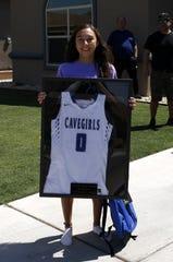 Carlsbad senior Baylee Molina displays her framed jersey during the Cavegirls Senior Basketball Celebration on May 9, 2020.