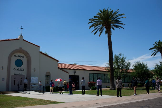 Parishioners wearing masks and practicing social distancing amid the COVID-19 pandemic receive Holy Communion at Gordon Hall at St. Gregory's Catholic Church in Phoenix. on May 10, 2020.