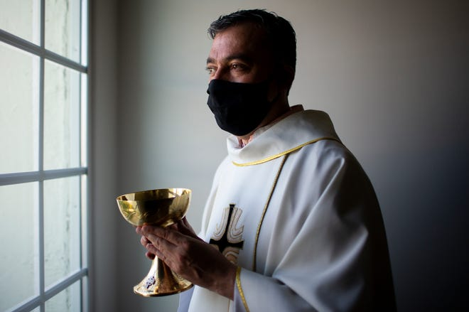 Father Andres Arango distributes Holy Communion while wearing a mask amid the COVID-19 pandemic at Gordon Hall at St. Gregory's Catholic Church in Phoenix on May 10, 2020.