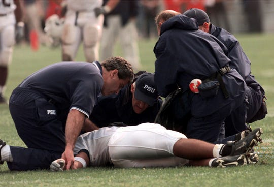 FILE - In this Saturday, Sept. 23, 2000 file photo, trainers examine Penn State cornerback Adam Taliaferro after he was injured in the fourth quarter of a game against Ohio State, in Columbus, Ohio. (AP Photo/Chris Putman,file)