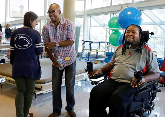 In this Wednesday, Sept. 10, 2014 file photo, Eric LeGrand, right, alumni of Rutgers University and Adam Taliaferro, center, alumni of Penn State University, both college football players who suffered serious spinal cord injuries on the field, react as child life specialist Tara Mohamed shows her Penn State shirt while visiting children at PSE&G Children's Specialized Hospital in New Brunswick, N.J.  (AP Photo/Mel Evans)