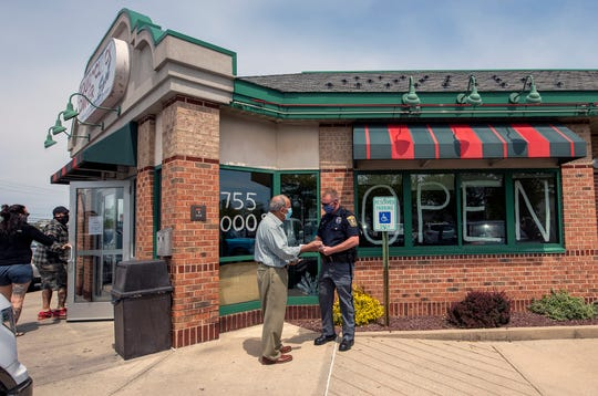 Owner Demos Sacarellos, left, talks with a Springettsbury Township Police officer after 911 received complaints about the Around the Clock Diner - East opening Sunday for sit-down service.