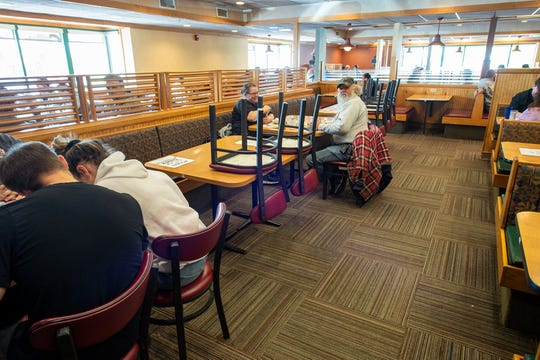 Family groups are separated by tables and signs that tell them to social distance at Around the Clock Diner - East in Springettsbury Township.