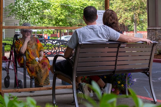 """Chris and Kim Johnston chat with Kim's mom, Marilyn Ramone, through the """"Looking Glass"""" at The Springs at Sunnyview in Salem, on May 10, 2020. The Johnston's brought Ramone a Mother's Day lunch of yellow curry chicken salad, soft-shell crab, and baba ghanoush from one of her favorite restaurants."""