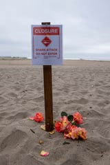 Roses are placed near a sign on the Manresa State Beach in memory of the surfer who lost his life in a shark attack yesterday afternoon. This photo was taken early morning on Sunday, May 10, 2020.