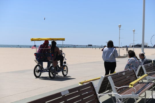 Tiffany Gilmore and Ryan Jones ride a bike kart on the tram-less boardwalk in Ocean City, Maryland, on May 10, 2020. The pair from Baltimore made the three-hour trip for fresh air and a change of scenery when they heard of the beach reopening.