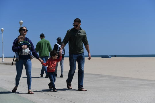 Parents Pam and Ryan Chase of Salisbury walk with their sons Wes, 1, and Juda, 4, on the newly reopened boardwalk in Ocean City, Maryland, on May 10, 2020.  The family looked to keep their distance from fellow visitors, noting mixed feelings on the reopening weekend.