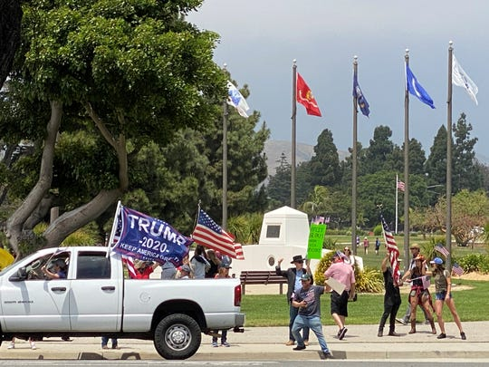 A rally Saturday in Ventura against continued coronavirus restrictions included supporters in vehicles circling the Ventura County Government Center as others gathered on sidewalks.