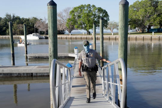 In this May 4, 2020, file photo, Park ranger Tyler Gagat wears a protective face mask as he monitors activity at the Flamingo boat ramp during the new coronavirus pandemic in Everglades National Park in Florida, as the park gradually reopens to the public in phases.