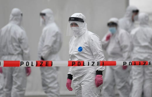 Members of a coronavirus testing station stand on the factory premises of the Westfleisch meat processing company in Hamm, western Germany, on May 10, 2020, as all workers of the company have to be tested on the novel coronavirus after a spike in cases at their slaughterhouse.