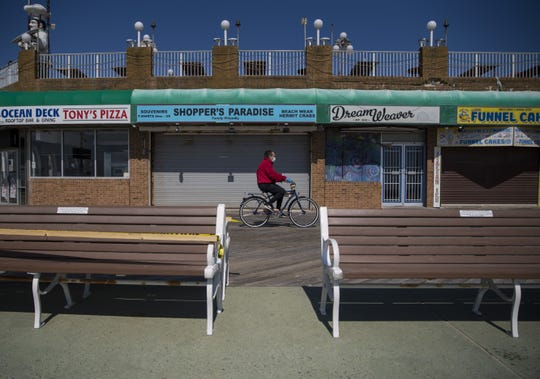 A man rides a bike on the boardwalk in Ocean City, Md., on May 10 as the area reopens after being closed for the coronavirus pandemic.