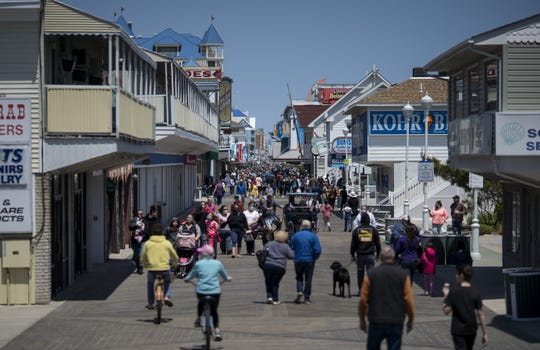 People walk on the boardwalk in Ocean City, Md., on May 10 as the area reopens from coronavirus shutdowns. A popular summer tourist destination, Ocean City reopened the beach but town officials said the initial reopening was designed primarily for locals.