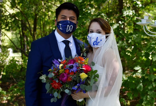 Newly married couple Rachel and Sebastian Vasquez wearing face masks, poses for pictures on May 9, 2020, after a ceremony at the Glencliff Manor in Rustburg, Va.  The Glencliff Manor officiates free, socially distanced ceremonies for couples left with no wedding plans during the coronavirus pandemic. Only ten people are allowed at each hour-long ceremony.