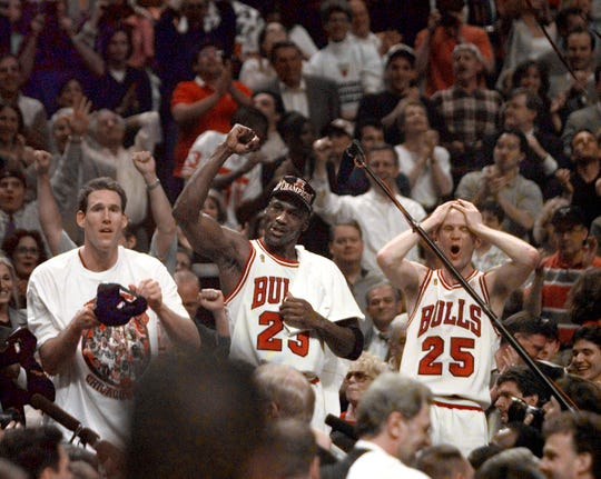 Chicago Bulls players Judd Buechler, left, Michael Jordan, middle, and Steve Kerr celebrate after winning the 1997 championship after defeating the Utah Jazz.