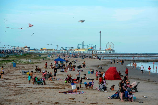 In this May photo, beachgoers enjoy the ocean in Galveston. One in five Texans said in a recent survey said they would rather stay home than go on a summer vacation this year if bars are closed.