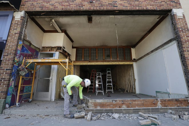 Steve Bodoh, an employee with Blue Sky Contractors, removes the facade of the former Vagabond Imports in downtown Appleton.
