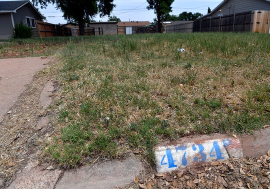 A grassy lot and painted curb address is all that remains one year later of the house that was at 4734 South Sixth Street when it was struck by a tornado almost a year earlier. Some residents rebuilt or remodeled homes while the damage was too much for others.