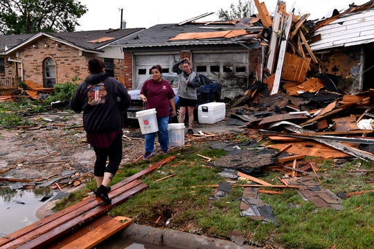 A Salvation Army worker carries relief supplies May 18 on South Sixth Street in Abilene. Relief organizations and citizen groups join forces to help after a tornado struck that morning.