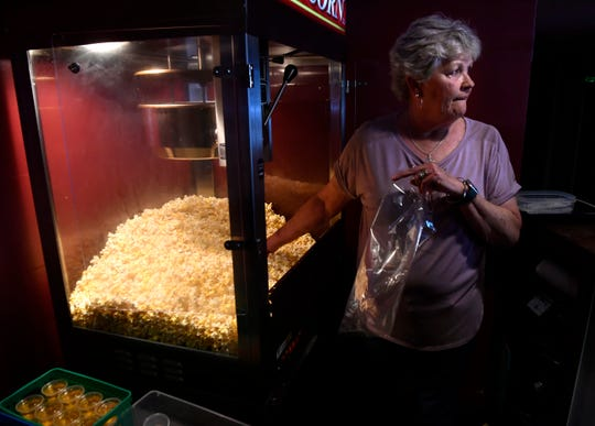 Marilee Denson, the manager of the Grand Theatre in Stamford, glances out the lobby door as she prepares to scoop popcorn into a bag May 1.