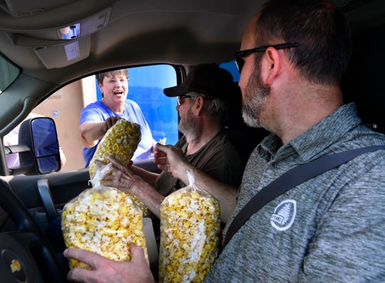 James and Cody Wilhite chat with Teresa Denson as they receive their bags of popcorn Friday May 1.