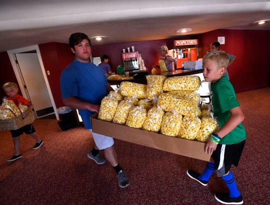 Luke Thane, 17, and Slayden Young,10, carry fresh bags of popcorn out of the lobby at Stamford's Grand Theatre May 1. Behind them, Slayden's seven-year-old brother Kase carries an armload of caramel corn. Unable to show movies during the pandemic, the Grand has started selling its popcorn curbside about twice a month.