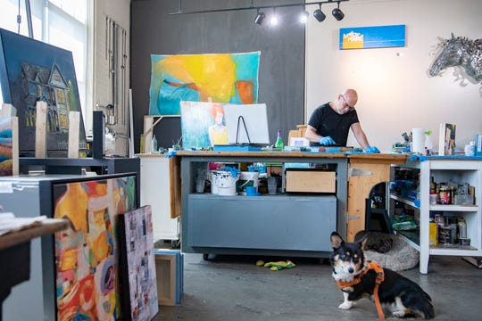 As his corgi, Chunk, patrols, artist Mark Bettis works on a piece at his studio in the River Arts District on May 7, 2020. Bettis has challenged himself to create two pieces of art a day which he posts for the artists support pledge.