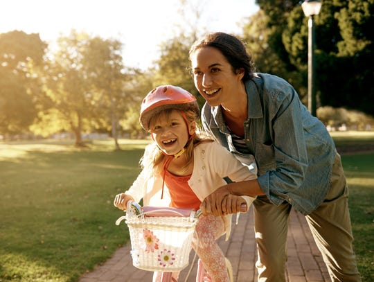 A woman teaches her daughter how to ride a bicycle at the park
