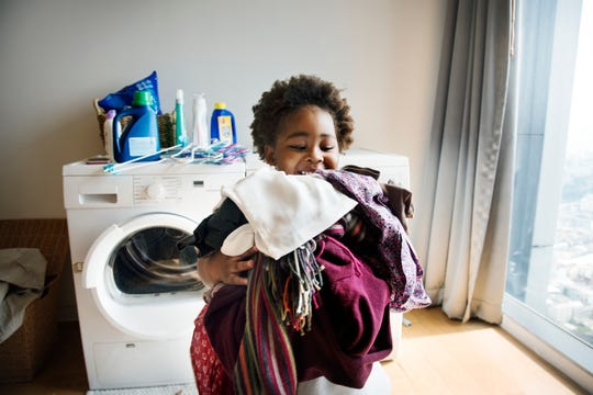 A child helps with the laundry