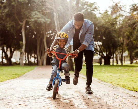 Father teaching his son how to ride a bicycle at park.