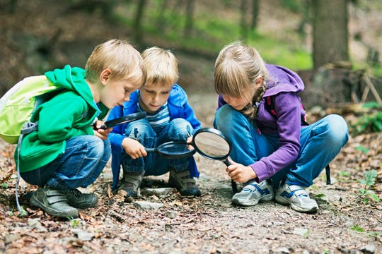 Kids with magnifying glasses exploring the nature.