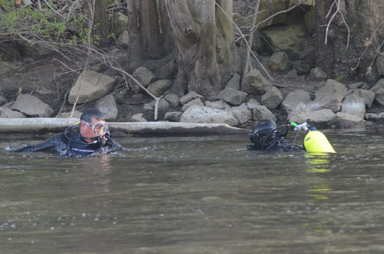 Divers Craig Swanson, left, and Dave Winder from the Calhoun County Dive Team, were among those who spent much of the week searching the Kalamazoo River for Eric Punzo. The body of the Olivet man was found Sunday.  Trace Christenson/The Enquirer