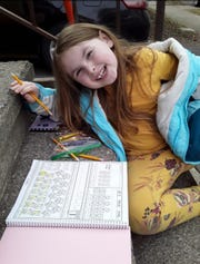 Cassie O'Neil, a first grade student at Binghamton's Theodore Roosevelt Elementary School, does schoolwork from home.