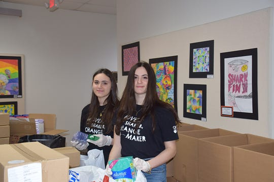 Alessia Stead, left, and her twin sister, Madison, sort through some of the personal care donations that are given out to students in need. They serve as co-presidents of the Girl Up Club at Union-Endicott High School and organized the drive to help students during the COVID-19 pandemic.