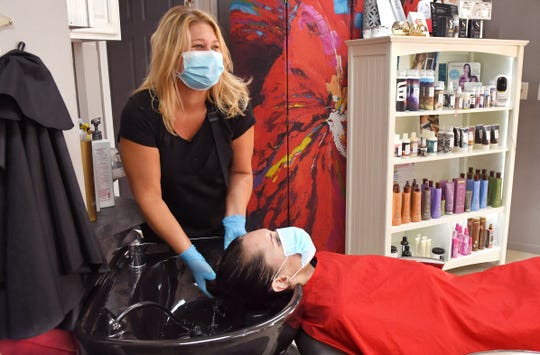 Stylist/manager Megan Wheeler washes Kennedy Monkress' hair Monday at Salon on Brevard in Cocoa Village.