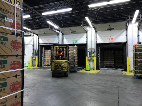 A forklift operator inside the Gloucester Marine Terminal loads a truck with pallets of bananas.