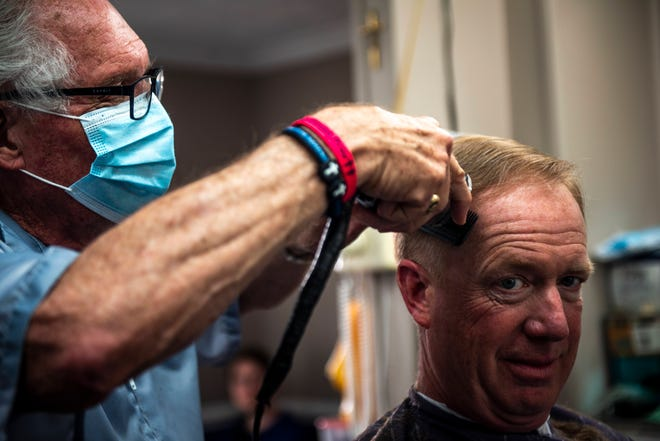 Karl Manke, 77, cuts the hair of Craig Wiker of Dowagiac at his barbershop in Owosso, on May 11, 2020.