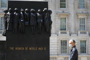 A pedestrian passes The Women of World War II statue, as the country is in lockdown to help stop the spread of coronavirus in London in this file photo from May 7, 2020. The British government performed an about-face on masks Monday, telling people to cover their mouth and nose in shops, buses and subway trains.