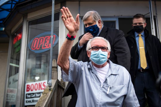 Karl Manke, 77, waves to supporters outside of his barbershop on West Main Street in Owosso Monday. Manke opened his barbershop and has hired Kallman Legal Group as his legal counsel because he was charged with criminal misdemeanor violations for allegedly violating Gov. Gretchen Whitmer's executive orders.