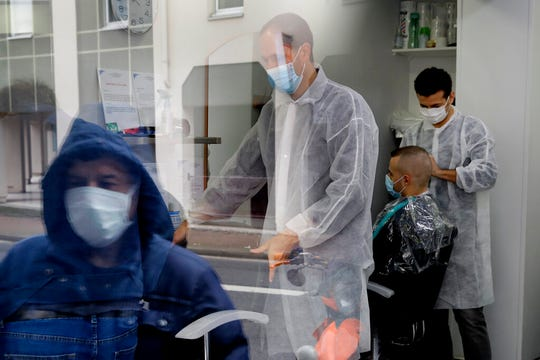 Men get a hair cut at a hairdressing salon in Sevres, outside Paris, Monday, May 11, 2020. Clothing stores, coiffures and other businesses large and small were reopening on Monday with strict precautions to keep the coronavirus at bay.