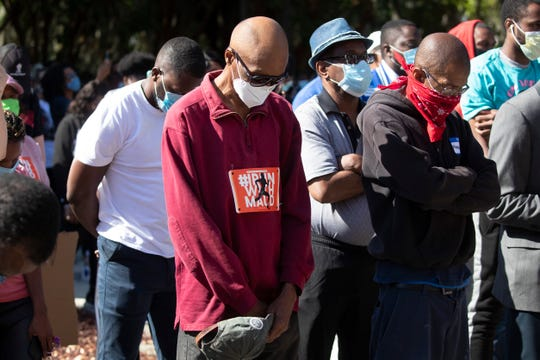 People pray during a rally to protest the shooting of Ahmaud Arbery, an unarmed black man Friday in Brunswick Ga.