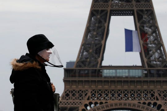 A man wears a protective mask as he walks near the Eiffel Tower, in Paris, Monday, May 11, 2020. The French began leaving their homes and apartments for the first time in two months without permission slips as the country cautiously lifted its lockdown.