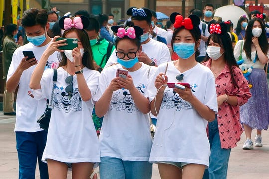 Visitors, wearing face masks, enter the Disneyland theme park in Shanghai as it reopened, Monday, May 11, 2020. Visits will be limited initially and must be booked in advance, and the company said it will increase cleaning and require social distancing in lines for the various attractions.