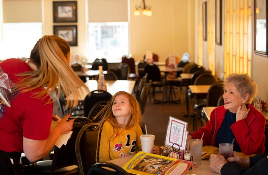 Nicole Brackett takes 7-year-old Lilly Page's spaghetti order as she dines with her great-grandparents Altia Wilcox, right, and Charles, not pictured, at Merry-Go-Round Restaurant at 2101 N. Fares Avenue Monday evening, May 11, 2020. It was the first day the restaurant had been open for nearly two months due to the coronavirus pandemic and the longtime patrons were happy to get a chance to visit again.