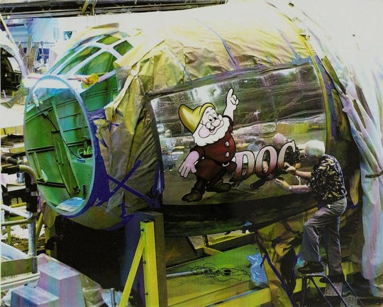 Owen Hughes paints the B-29 Doc's Friends bomber in 2000. Hughes painted several air planes with pinups and logos to inspire morale during World War II.